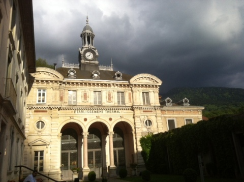 L'accès aux thermes d'Uriage jouxtant le Grand Hôtel. Derrière s'élèvent les contreforts de la Belledonne, où est puisée l'eau thermale (ph. VD)